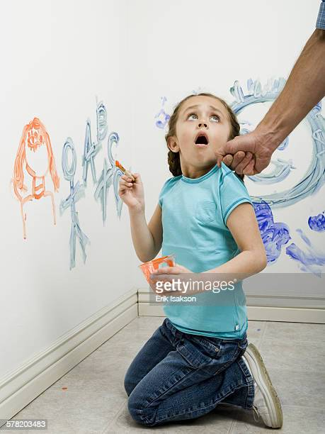 Close-up of a man pulling a girls top while painting on a wall