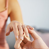 Close-up of a man putting an engagement ring on to a woman's finger