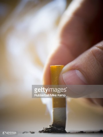 Close-up of a man putting out a cigarette