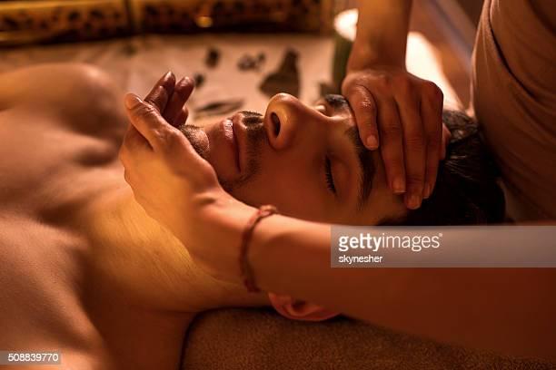 Close-up of a man receiving facial massage at spa.