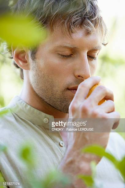 Close-up of a man smelling a lemon