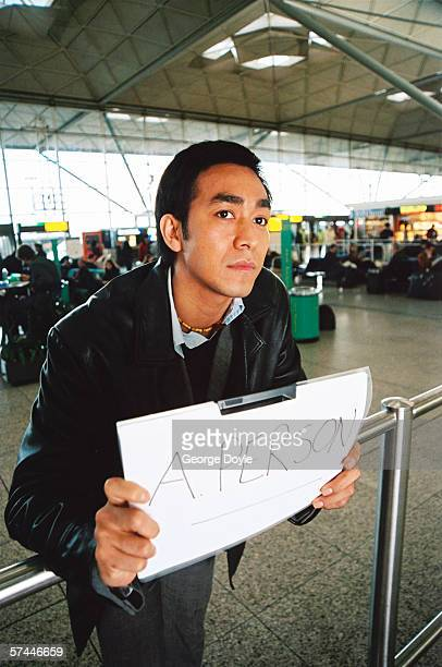 close-up of a man standing at the airport arrivals holding a placard