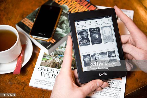A closeup of a man using a Kindle Paperwhite ereader in a cafe setting on January 14 2013