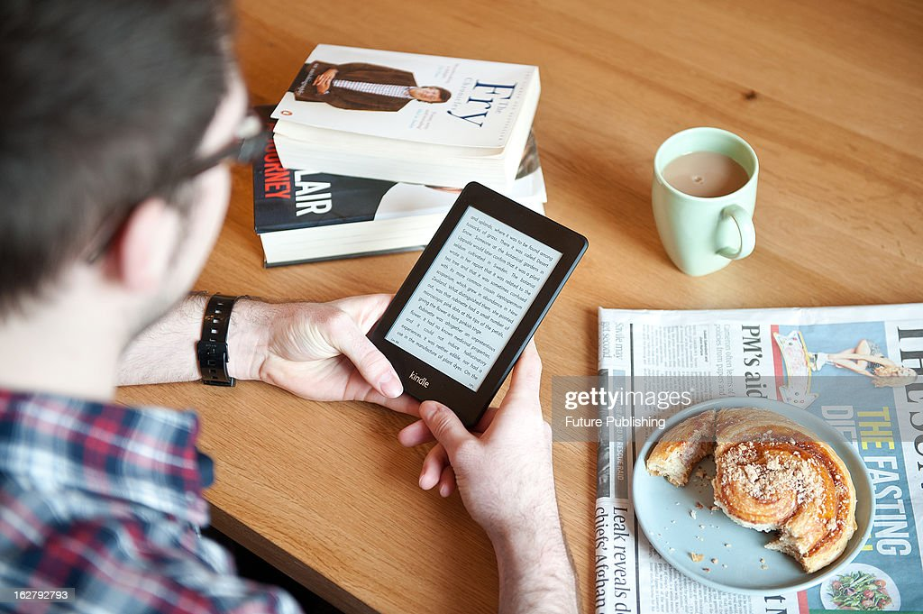 A close-up of a man using a Kindle Paperwhite e-reader whilst enjoying morning coffee, January 17, 2013.