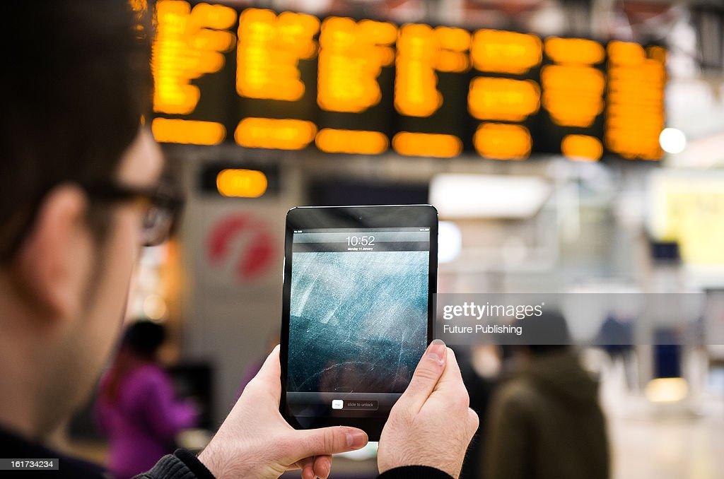 A close-up of a man using an Apple iPad Mini tablet computer at London's Paddington Station on January 14, 2013.
