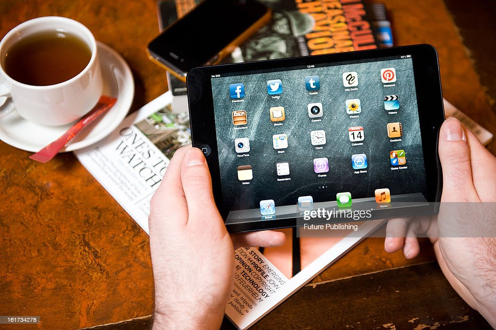 A close-up of a man using an Apple iPad Mini tablet computer in a cafe setting on January 14, 2013.