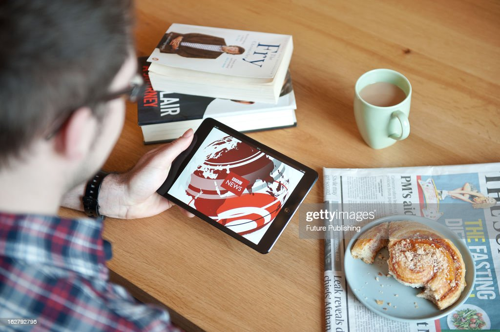 A close-up of a man using an Apple iPad Mini tablet computer to read the news, January 17, 2013.