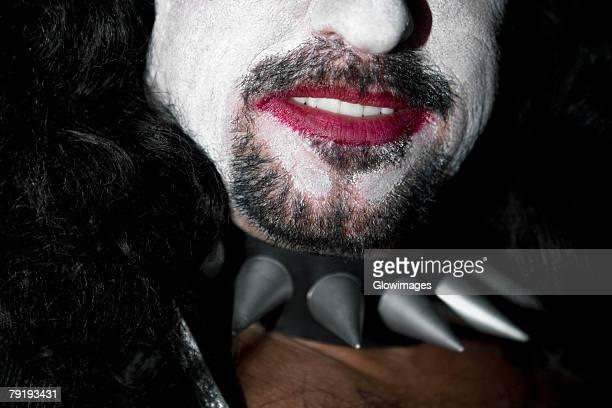 Close-up of a man wearing a spikey pet collar
