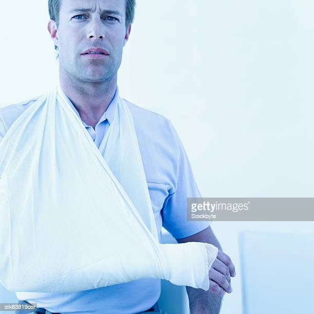 Close-up of a man with a fractured arm in a cast and sling