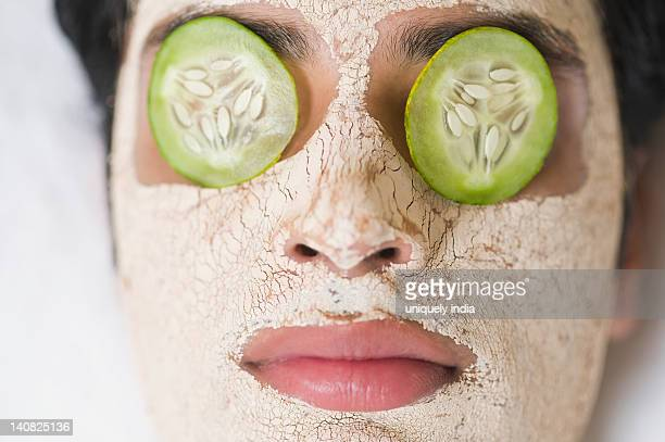 Close-up of a man with facial mask and cucumber slices on eyes