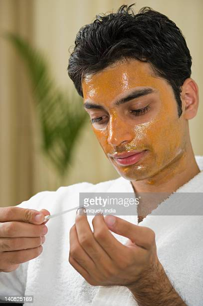 Close-up of a man with peel off mask filing his nails