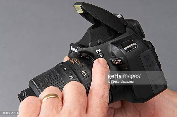 A closeup of a man's finger pushing the flash button on a Nikon D3100 DSLR camera photographed during a studio shoot for NPhoto Magazine August 31...