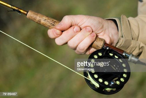 Close-up of a man's hand holding a fishing rod : Foto de stock