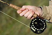 Close-up of a man's hand holding a fishing rod