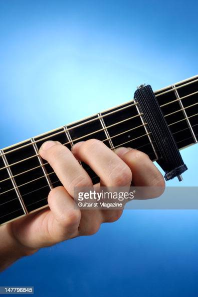 A closeup of a man's hand playing a D major chord on an acoustic guitar using a capo on the second fret during a studio shoot for Guitarist Magazine...
