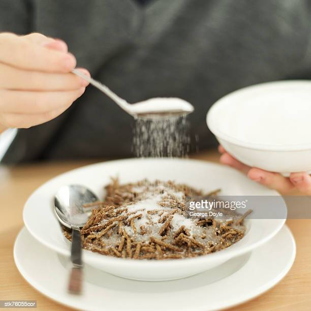 close-up of a man's hand sprinkling sugar on a bowl of cereal