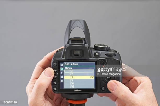 A closeup of a man's hands adjusting the manual flash power of a Nikon D3100 DSLR camera photographed during a studio shoot for NPhoto Magazine...