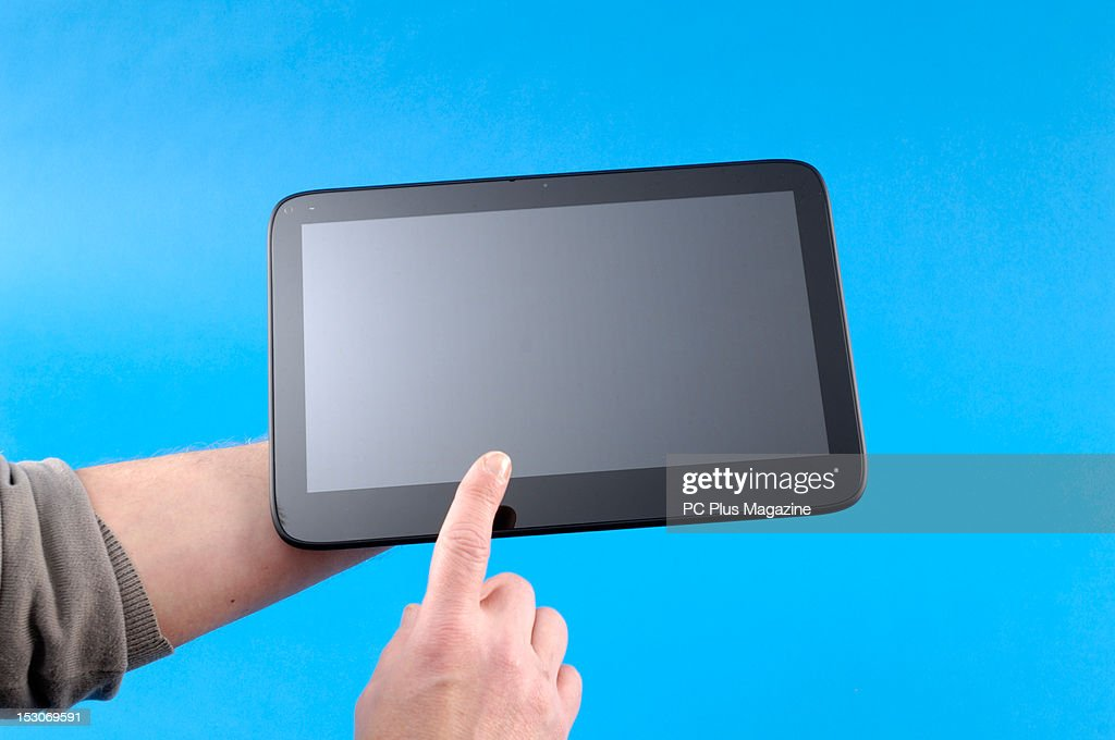 A close-up of a man's hands as he uses a Windows tablet computer, photographed during a studio shoot for PC Plus Magazine, March 2, 2012.