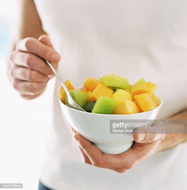 close-up of a man's hands holding a bowl of cut fruit