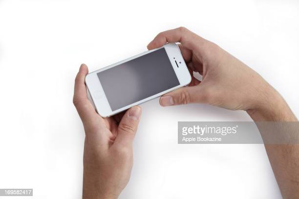 A closeup of a man's hands holding a white Apple iPhone 5 smartphone taken on October 24 2012