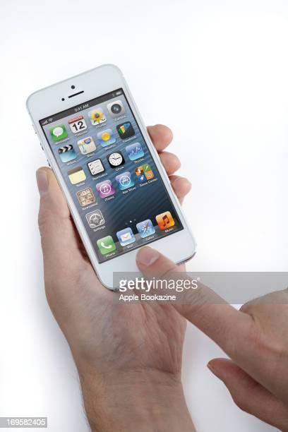 This image has been digitally manipulated A closeup of a man's hands using a white Apple iPhone 5 smartphone taken on October 24 2012