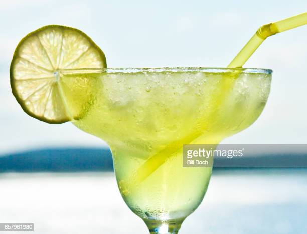 Closeup of a margarita by the ocean with alime slice and a straw