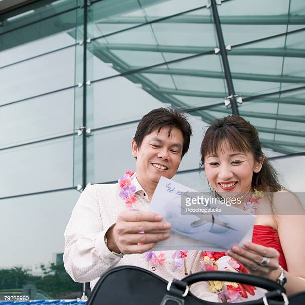 Close-up of a mature couple holding an airplane ticket and smiling