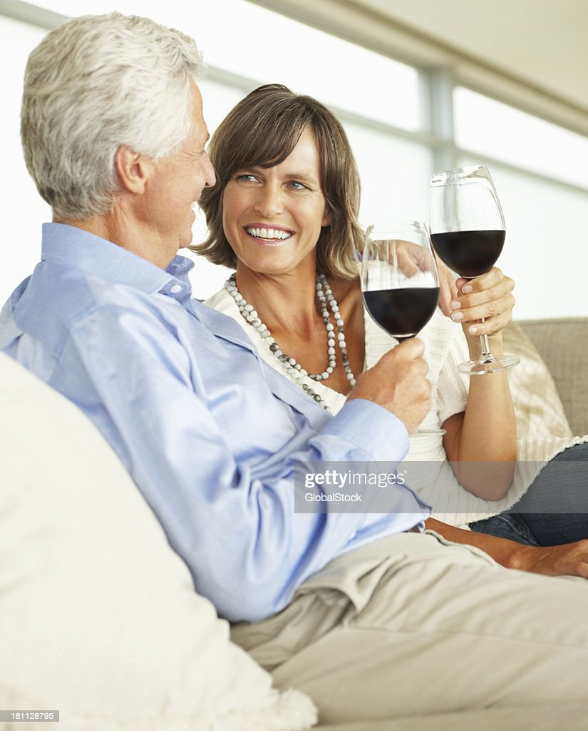 Close-up of a mature couple holding wineglasses : Stock Photo