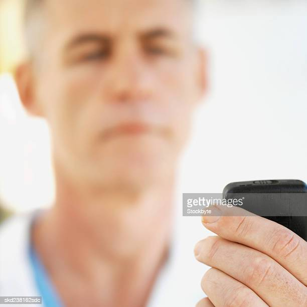 Close-up of a mature doctor holding pager