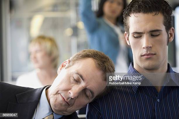 Close-up of a mature man asleep on a young man's shoulder