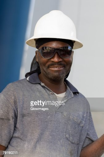 Close-up of a mature man with a pair of eyeglasses and a hardhat : Foto de stock