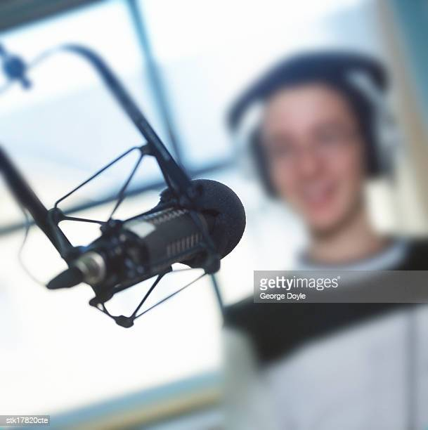 close-up of a microphone in a recording studio with a man wearing headphones; blurred