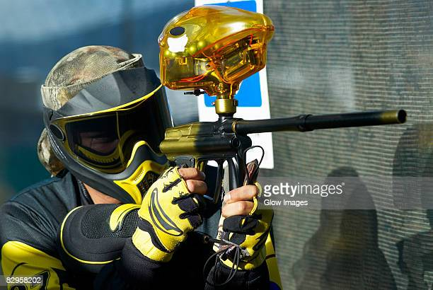 Close-up of a mid adult man aiming with a paintball gun