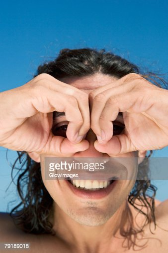Close-up of a mid adult man making circles around his eyes with fingers : Foto de stock