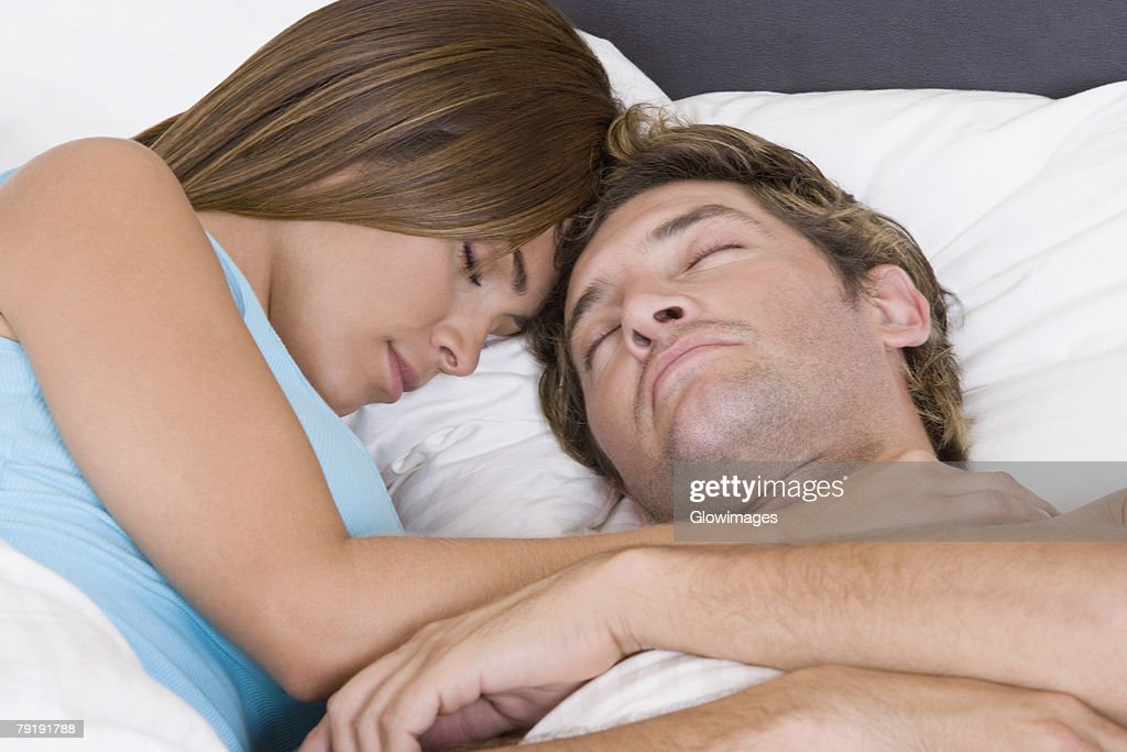 Close-up of a mid adult man sleeping on the bed with a young woman : Foto de stock