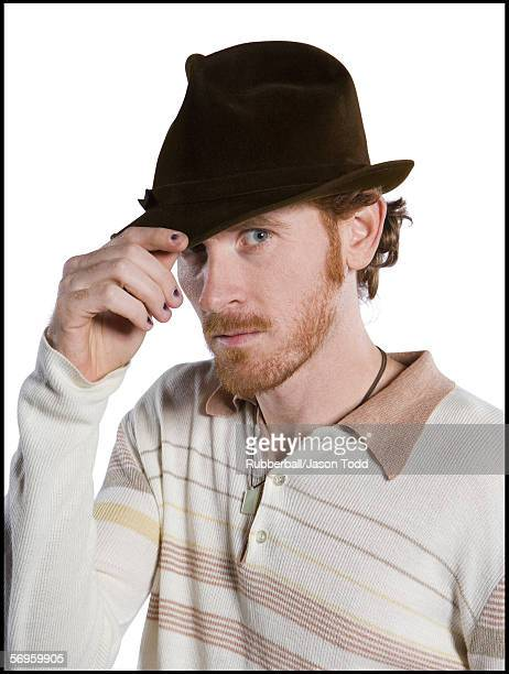 Close-up of a mid adult man touching his hat