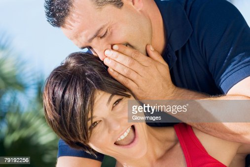 Close-up of a mid adult man whispering into a mid adult woman's ear : Foto de stock