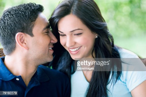 Close-up of a mid adult man whispering into a young woman's ear : Foto de stock