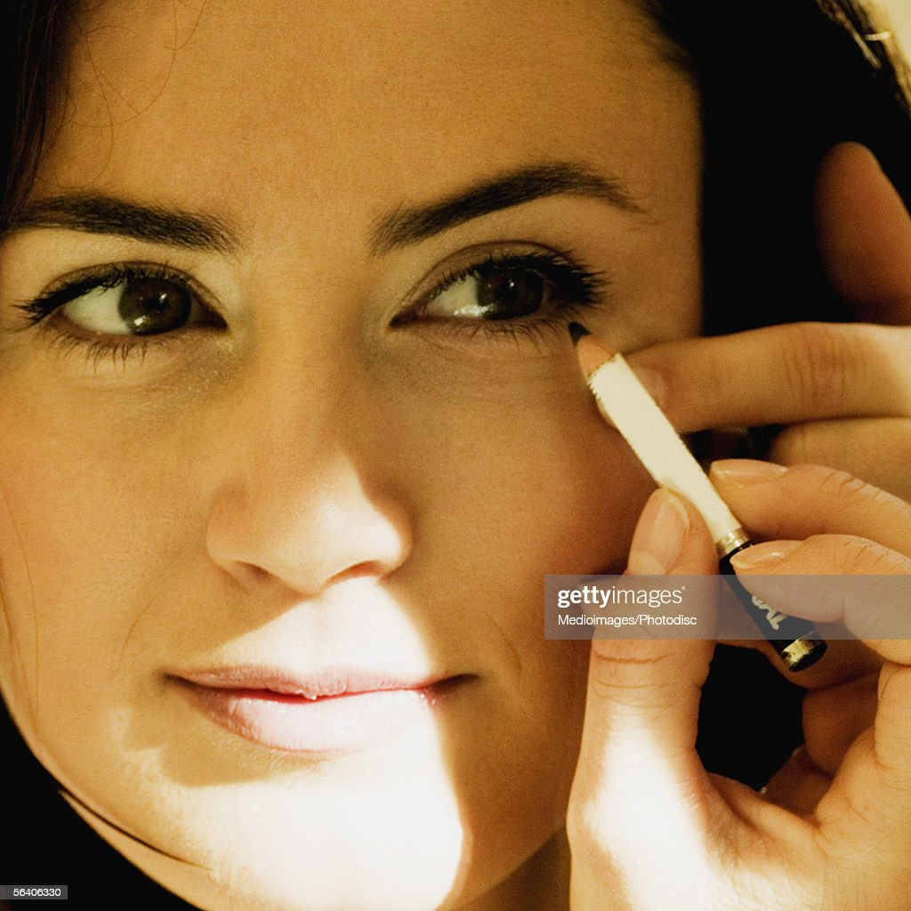 Close-up of a mid adult woman applying eye liner : Stock Photo