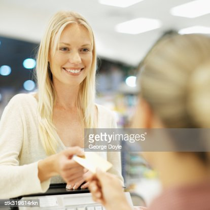 close-up of a mid adult woman at a checkout counter in a supermarket : Stock Photo