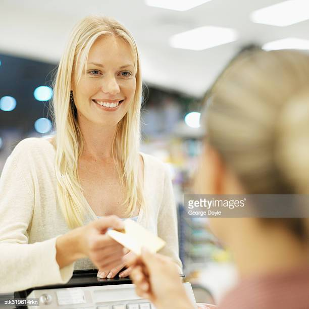 close-up of a mid adult woman at a checkout counter in a supermarket