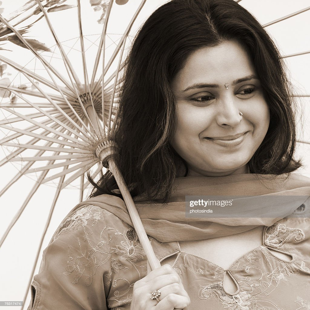 Close-up of a mid adult woman holding a parasol and smiling