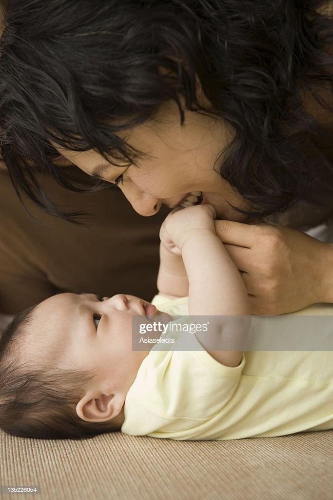Close-up of a mid adult woman playing with her daughter : Stock Photo