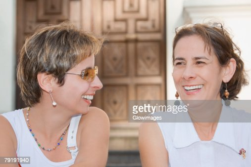 Close-up of a mid adult woman sitting with a mature woman and laughing : Stock Photo