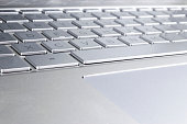 Closeup of a modern silver laptop computer keyboard. Laptop keyboard. Detail of the new and ergonomic computer keyboard.
