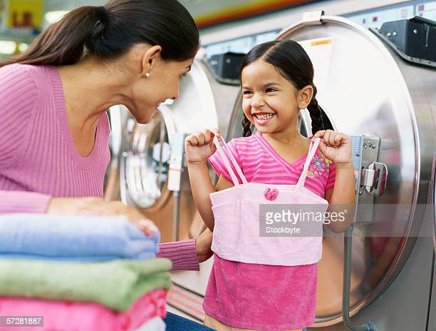Close-up of a mother and her daughter in a launderette