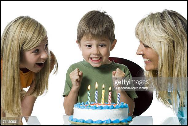Close-up of a mother and her two children in front of a birthday cake