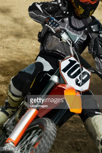 Close-up of a motocross rider riding a motorcycle : Stock Photo