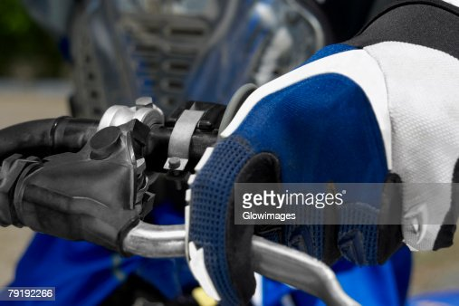 Close-up of a motocross rider's hand on the handlebar of a motorcycle : Stock Photo