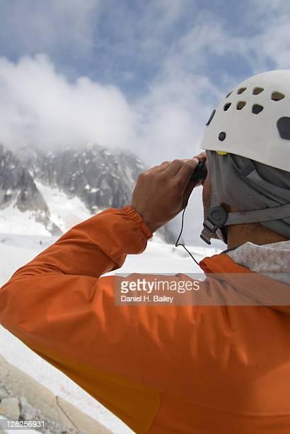 Closeup of a mountain climber looking through binoculars